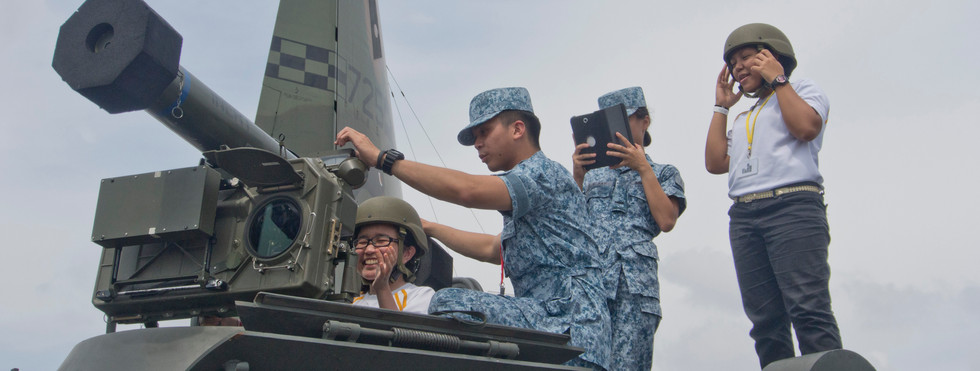 Young woman trying an anti-tank missile at an arms fair in Singapore