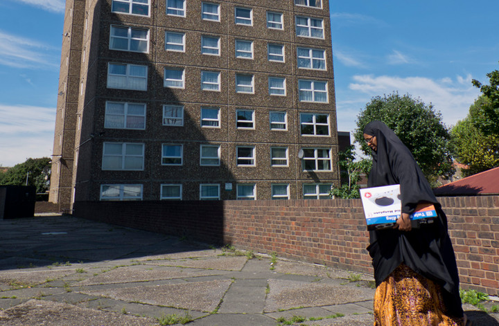 Resident of tower block with gas leak emergency carrying electric hot plates donated by council in Southwark, London