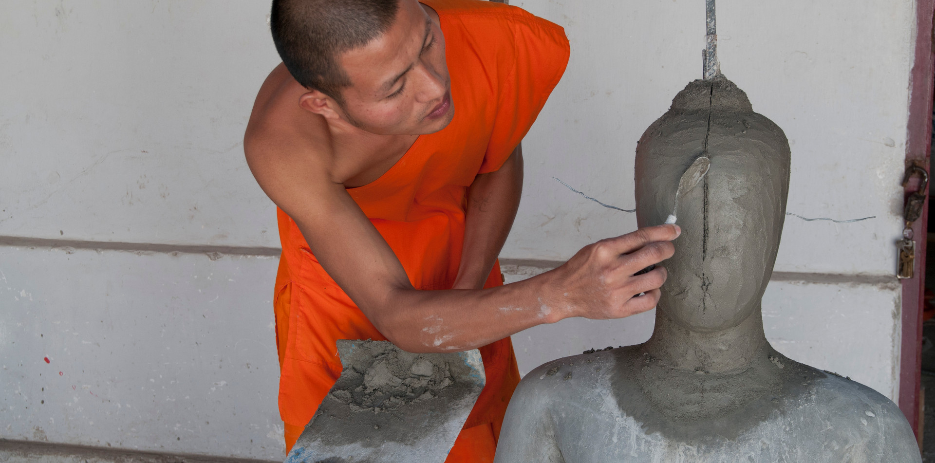 Monk making statue of Buddha in a temple in Laos