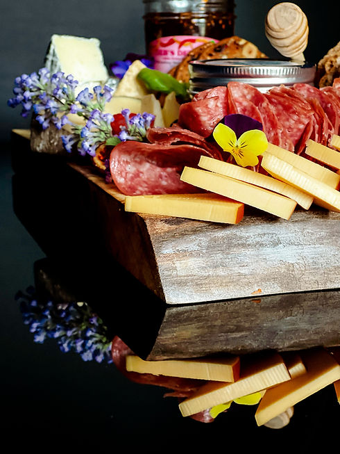 A beautiful charcuterie board with honey, cheese, jam, salami, and edible flowers.