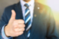 Guy in a suit with a thumbs up.