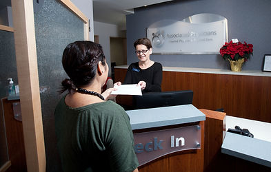 Receptionist handing a paper to a patient.