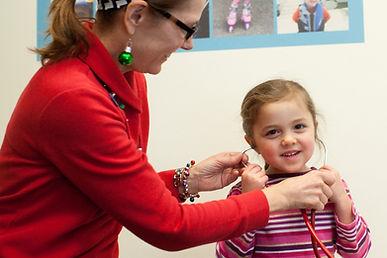 Pediatric nurse putting stethoscope on child patient.