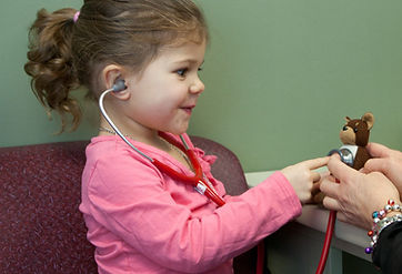 Young child using stethoscope on toy bear.