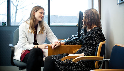 Internist Dr. Fothergill sitting with a patient.