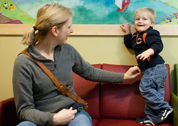 Mother and child smiling in the pediatrics waiting room.