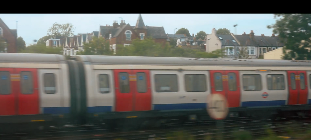 London Underground train in motion passing in front of a row of houses.