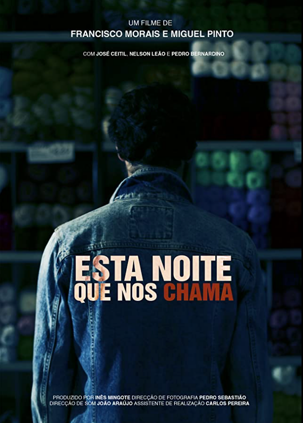 A man in a denim jacket stands with his back to the camera looking at  the shelves inside a wool shop.