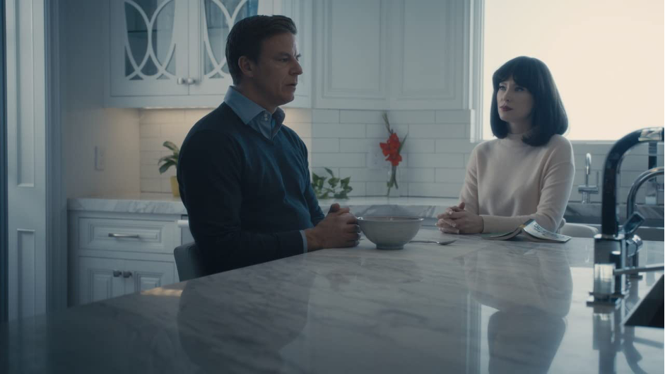 A man sits at his kitchen breakfast bar with a woman sitting next to him listening purposefully.