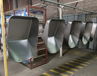 Wheelbarrows hanging prior to powdercoating