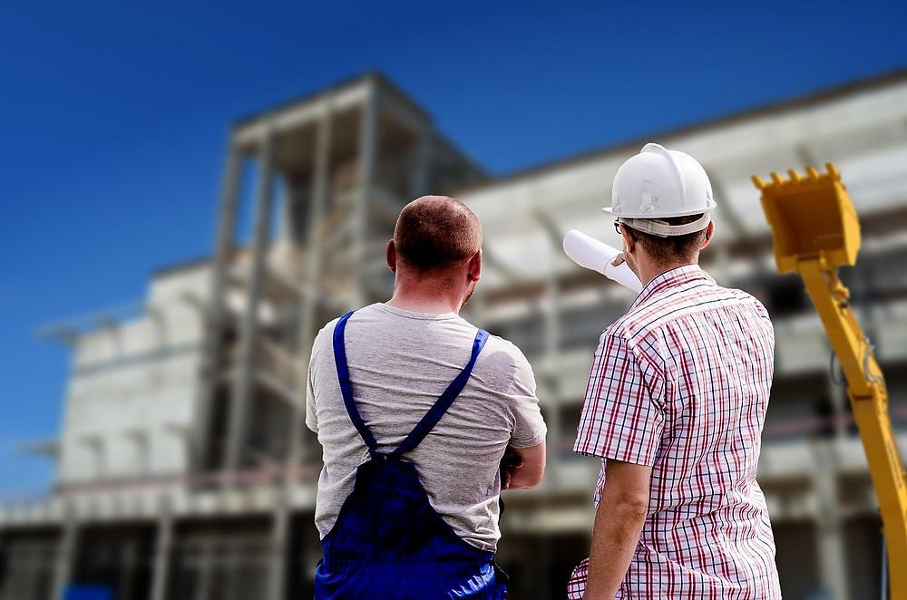 Ouvrier et technicien devant un bâtiment en construction