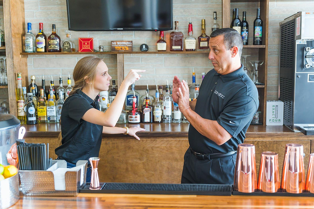 Mixologist and bartender arguing in the middle of a bar