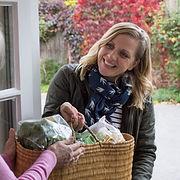 Female Neighbor Helping Senior Woman Wit
