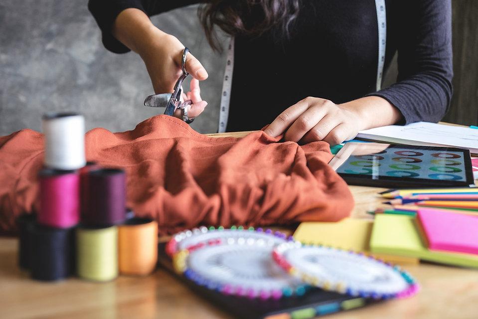 fashion design school student cutting fabric