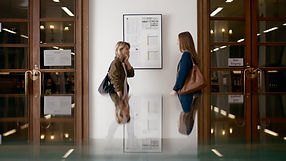 Two happy, young women in library. Shot by Tjark Lienke for BMW.