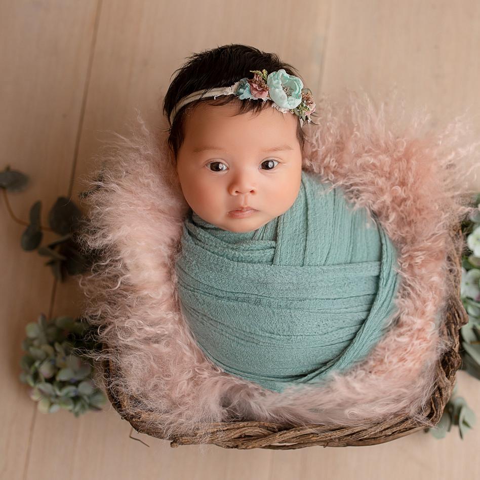 baby im Kukon in türkis rosa