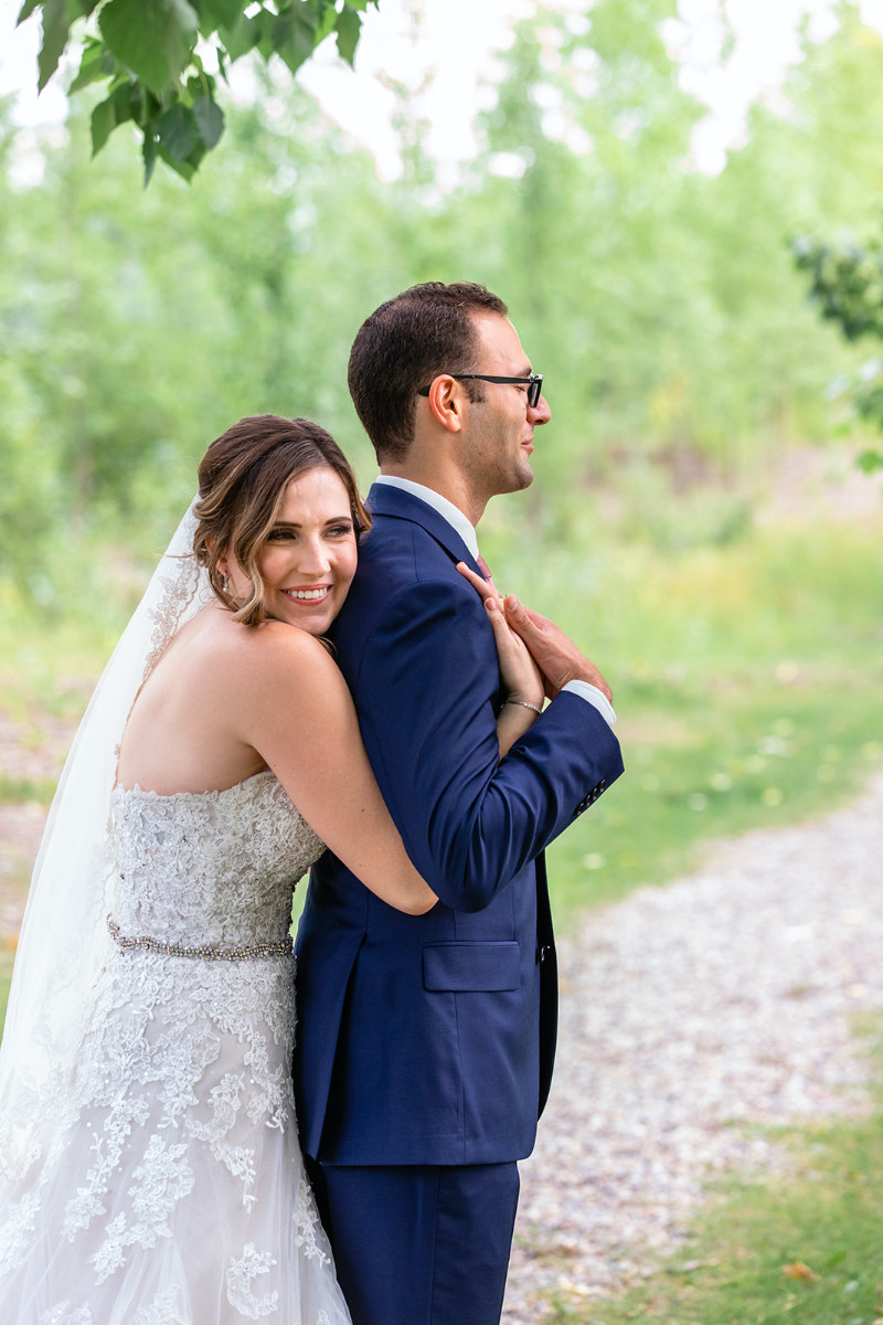 bride hugs groom from behind on their Calgary wedding day before the ceremony