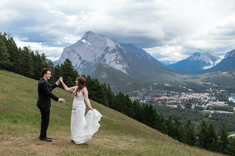 mountain elopement in Banff with bride and groom dancing in the photo