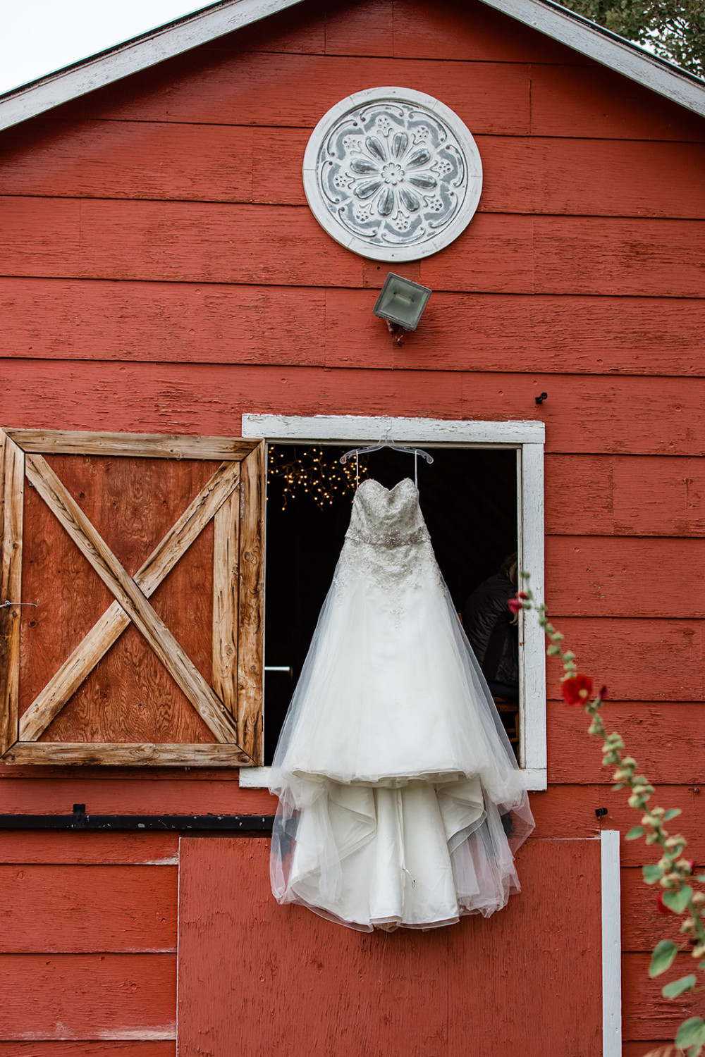 Wedding Dress hangs outside a rustic red barn wedding venue in Calgary