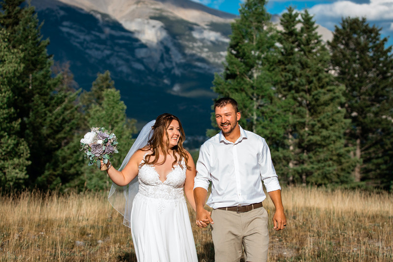 Canmore wedding photography bride and groom photos in a field with the Rocky Mountains in the background