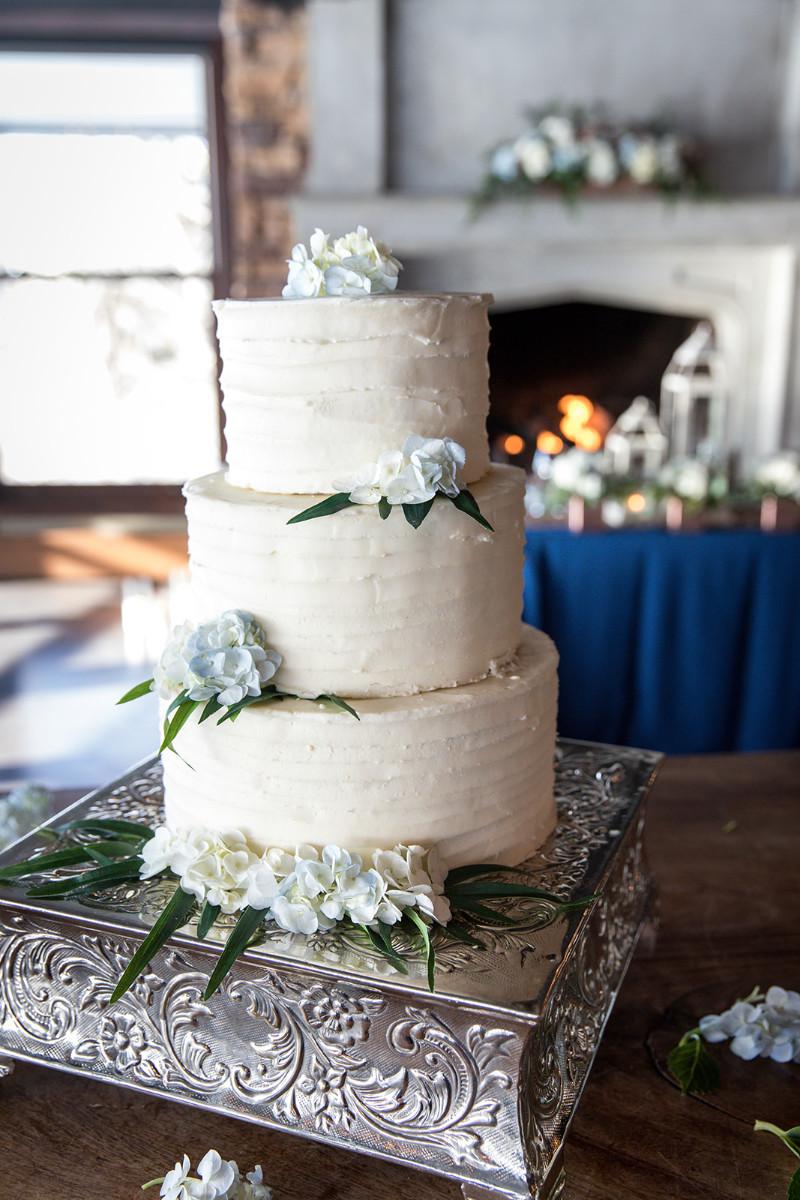 3 tier white wedding cake with greenery