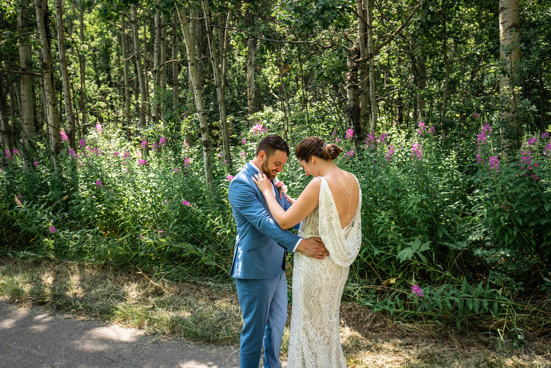 groom looks at bride during first look wedding photos