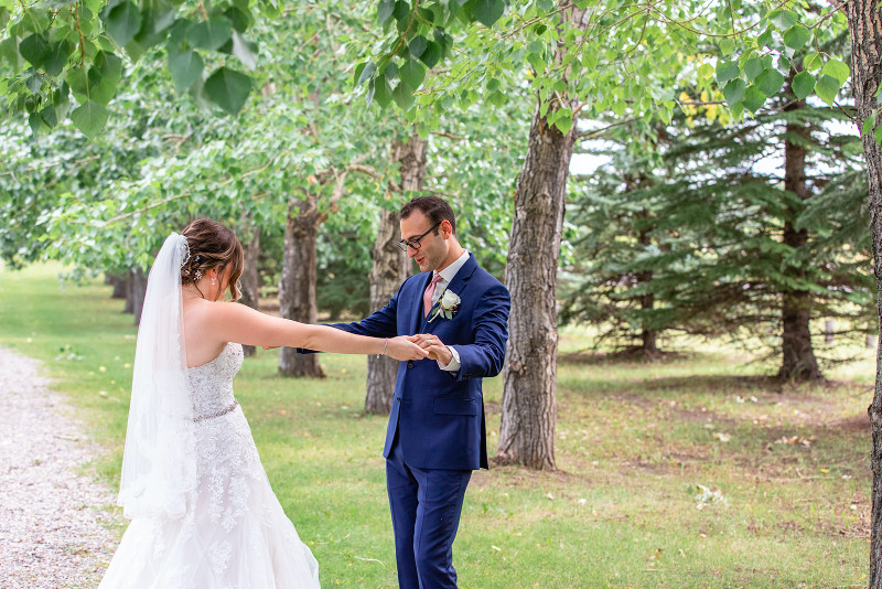Groom checks out bride during first look wedding photos in Alberta