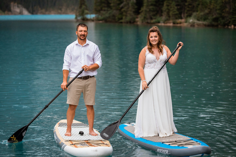 bride and groom adventure paddle board on a Rocky Mountain lake