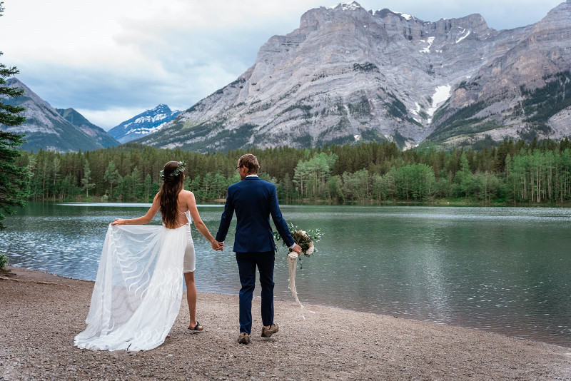 bride and groom overlook a lake in the middle of the Rocky Mountains