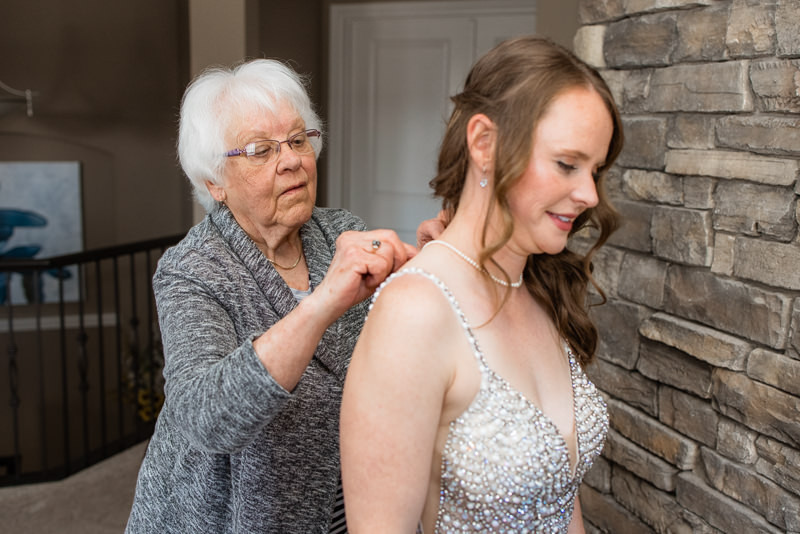 grandmother helps bride with her necklace