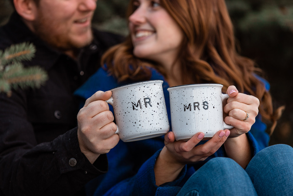 engaged couple holding mr and mrs coffee cups planning to elope