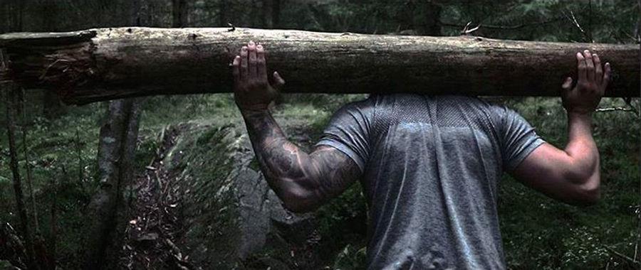 strong man carrying a log