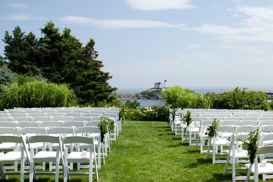 Ceremony aisle with Nubble Lighthouse backdrop in York, Maine. Simple outdoor wedding ceremony aisle florals