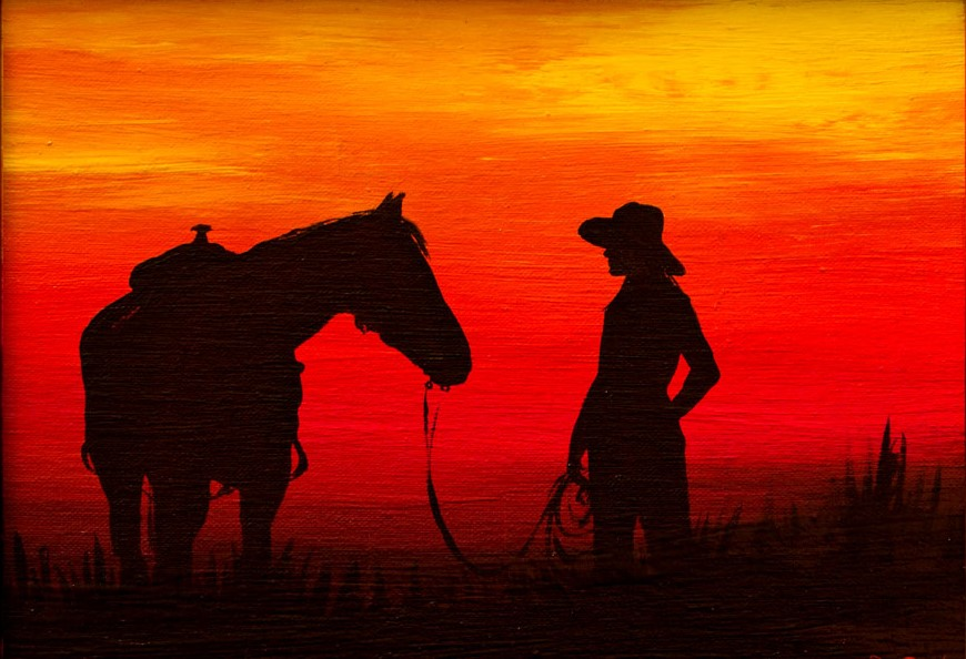The cowgirl and her horse at sunset