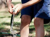 maos-e-pernas-de-uma-crianca-segurando-uma-mangueira-com-agua.jpg