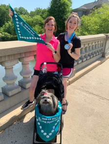 Sharon and Marilyn Dyess rocking race swag with their 4 legged friend!