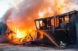 Fireman extinguishes a burning old woode