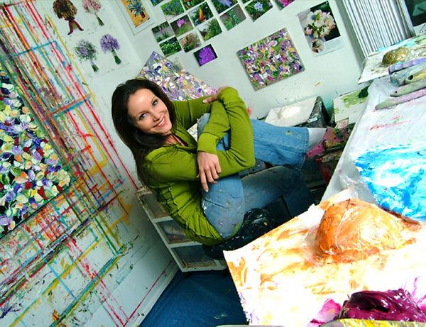 renea menzies in her studio gallery painting her art