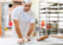 Padeiro sovando massa em bancada com farinha
