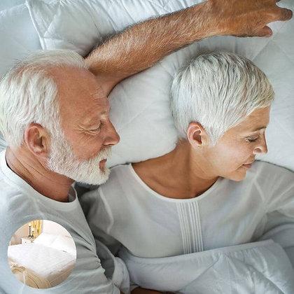 זוג קשישים ישנים על מיטה עם מגן מזרן זוגי של ברולי