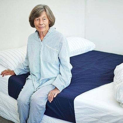 אישה קשישה יושבת על מיטה וחצי המוצעת במגן מזרן סופג של ברולי