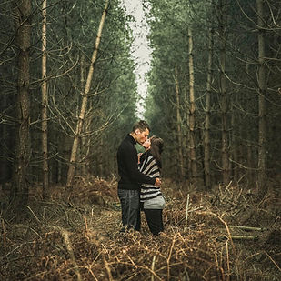 man and woman kissing in forest