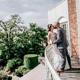 Bride and groom kissing on balcony