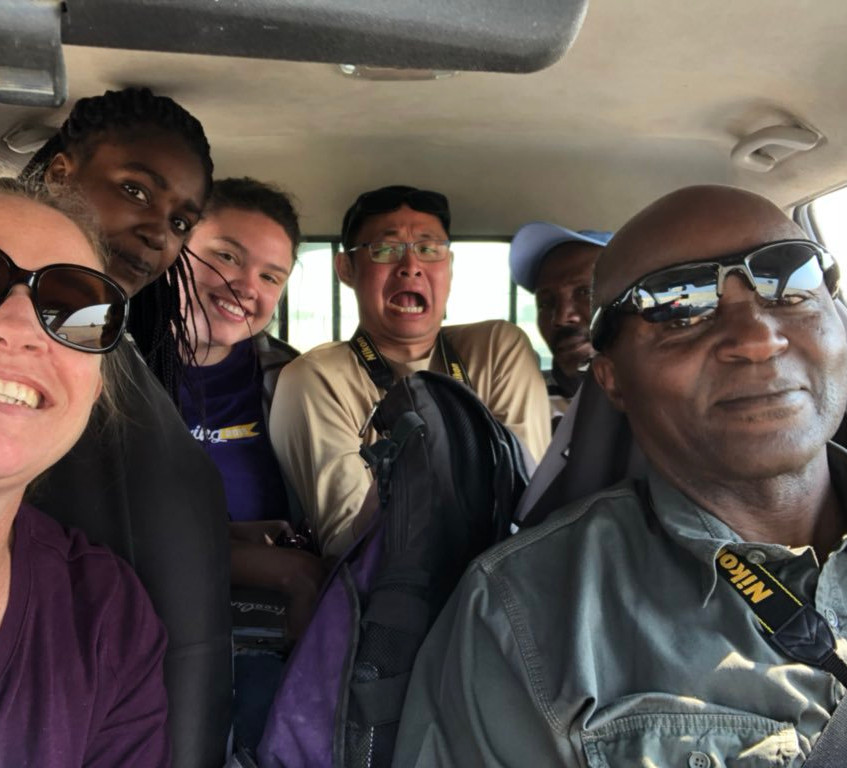 Four people squeezed at the back seats of a car (photo credit to Wendy Turner)