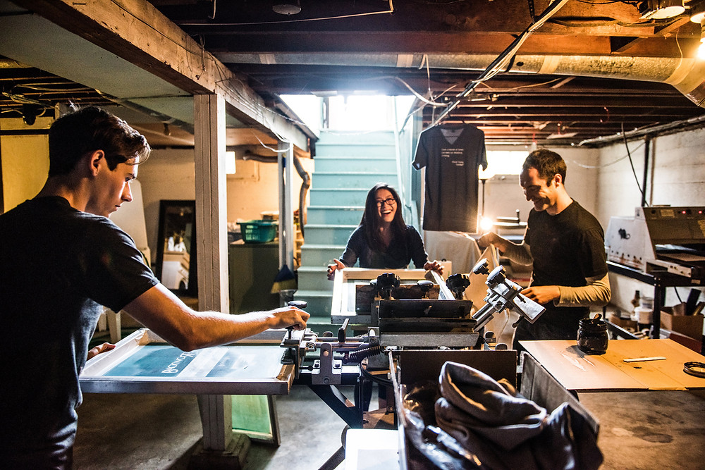 Phillip, Jenny, and Matty all working on the four-color screen printing press. Color photo.