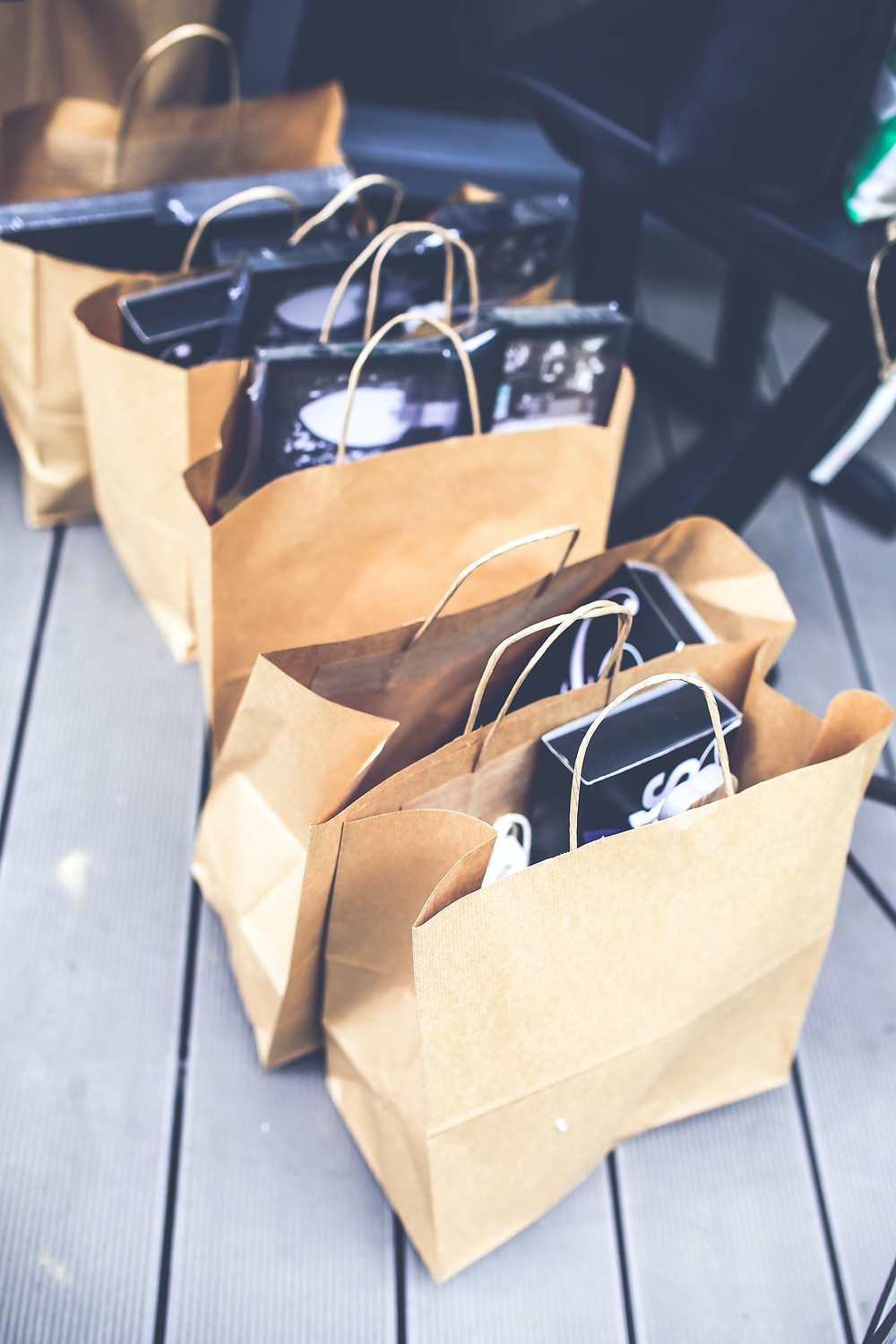 Multiple brown shopping bags filled with items set on the floor