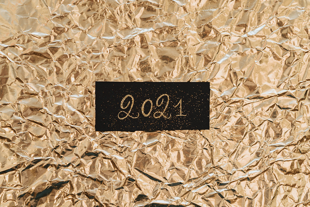 2021 cut out from a black block over a crumpled gold background