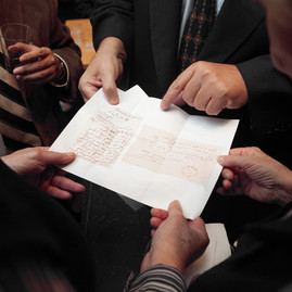 Some of the scholars visiting were examining a copy of an old document.