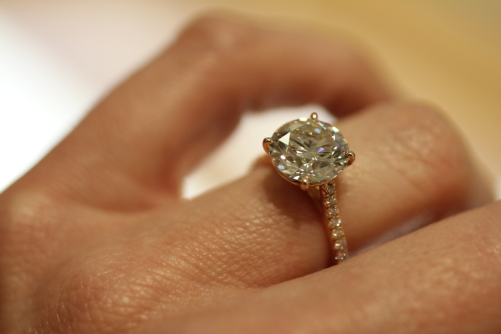 engagement ring, rose gold, round brilliant diamond solitaire, pave set accent diamonds down the side of the band shank