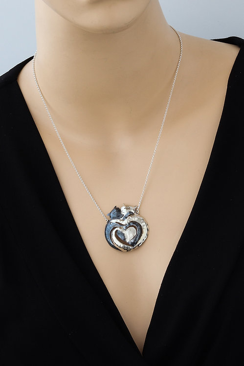 Picture of a silver pendant two cats hugging. Handmade Israeli art